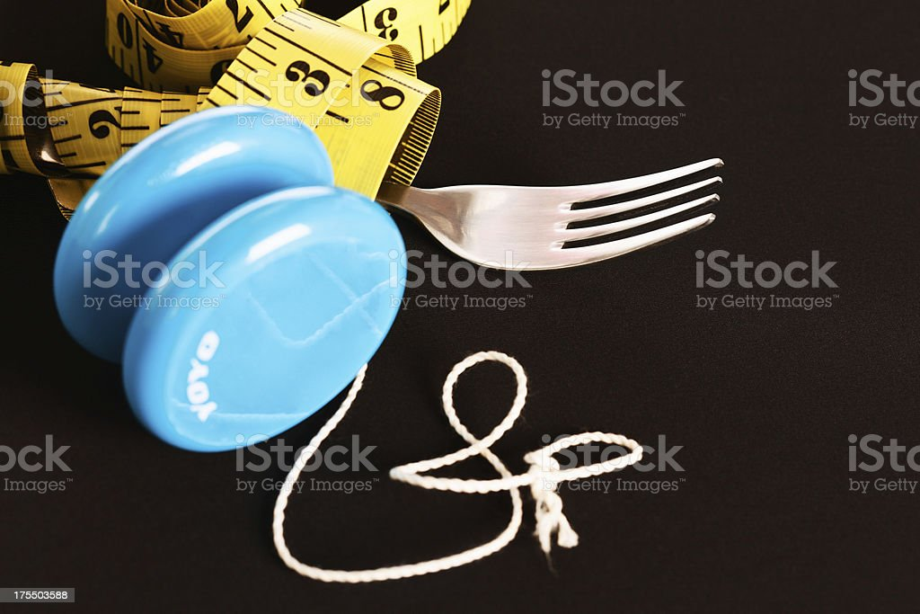 Futility of yo-yo dieting illustrated with fork and tape measure stock photo