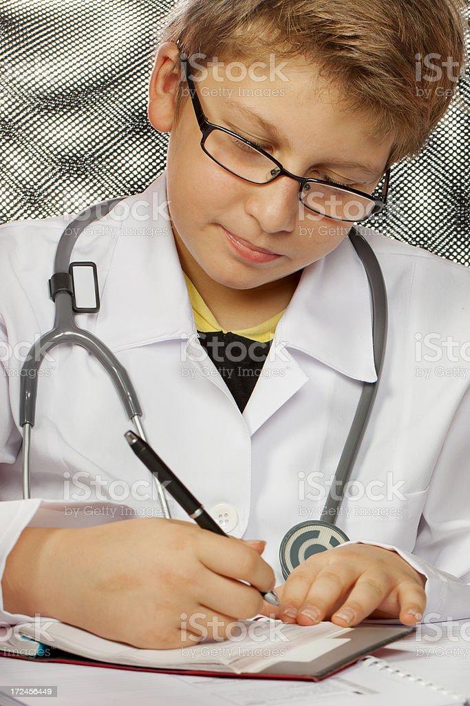 Future cute doctor writes a prescription royalty-free stock photo