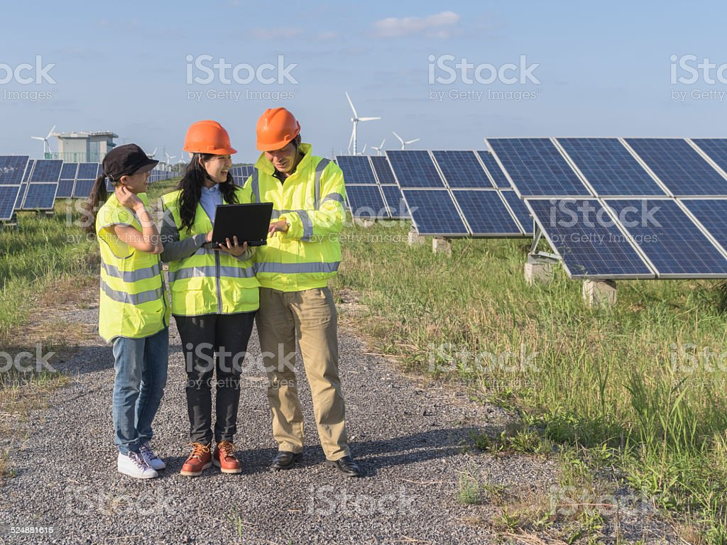 workers at a renewable energy plan, young asian engineers working in...