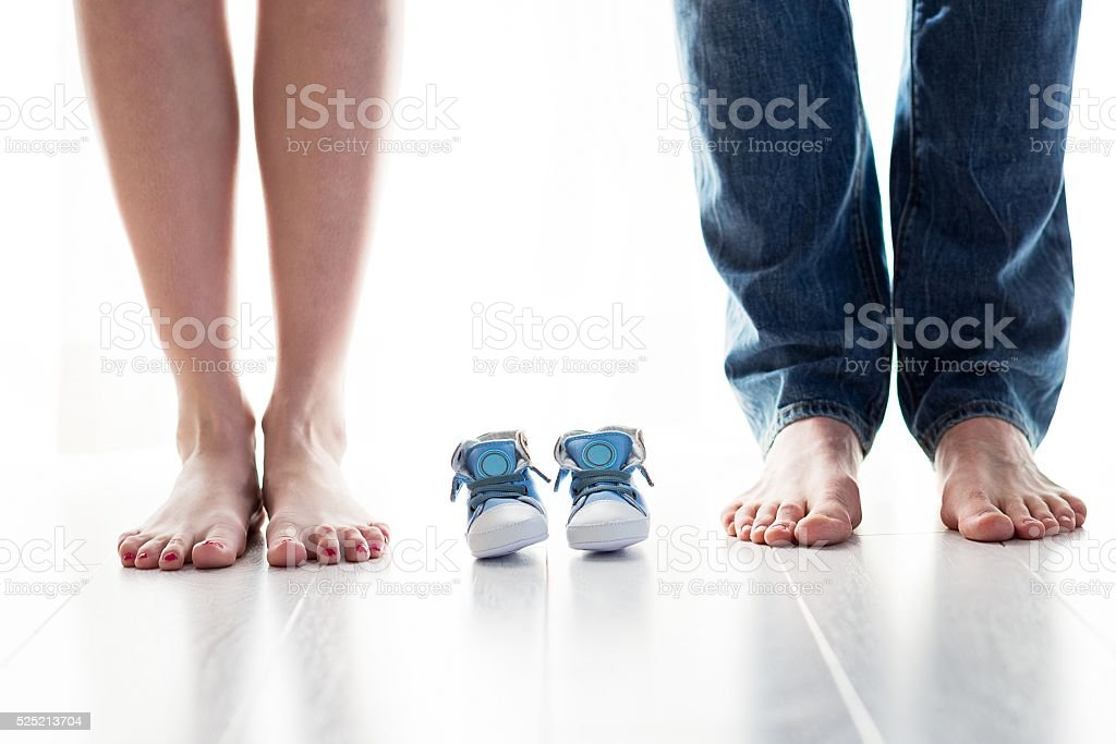 Future mom and dad feet with little baby shoes stock photo