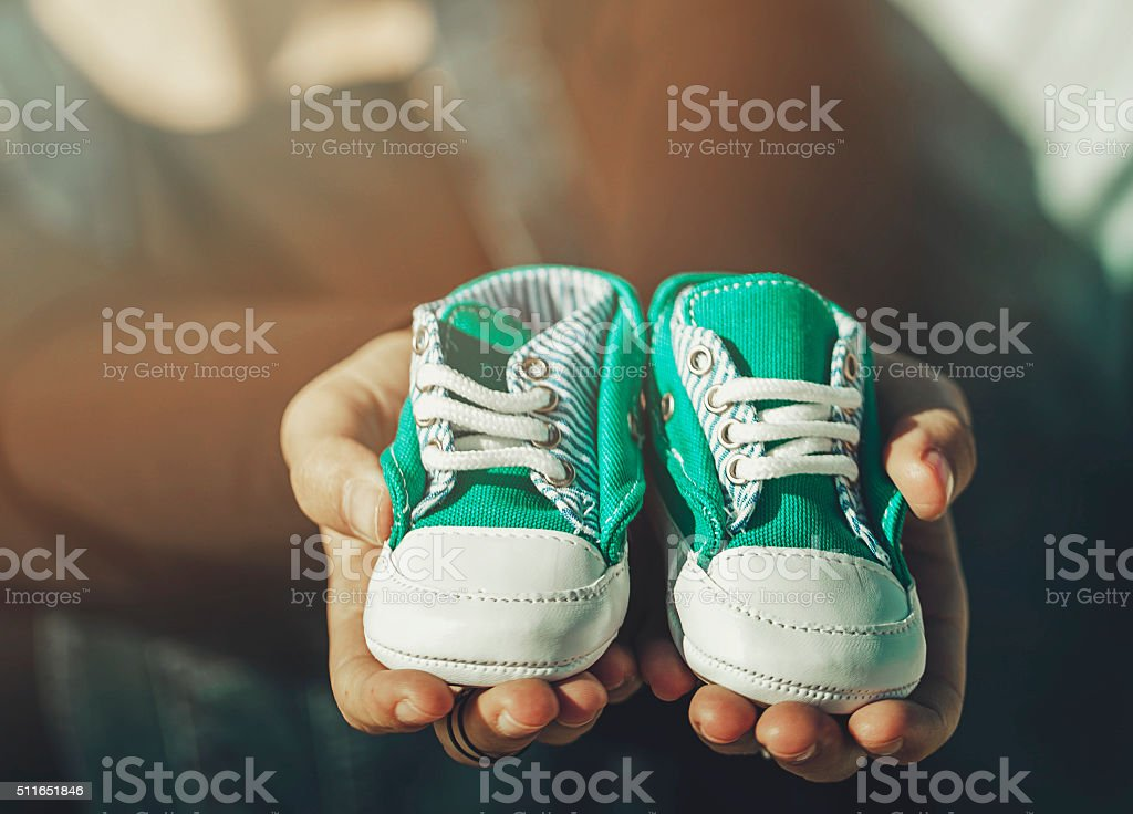 Future parents holding a pair of little shoes stock photo