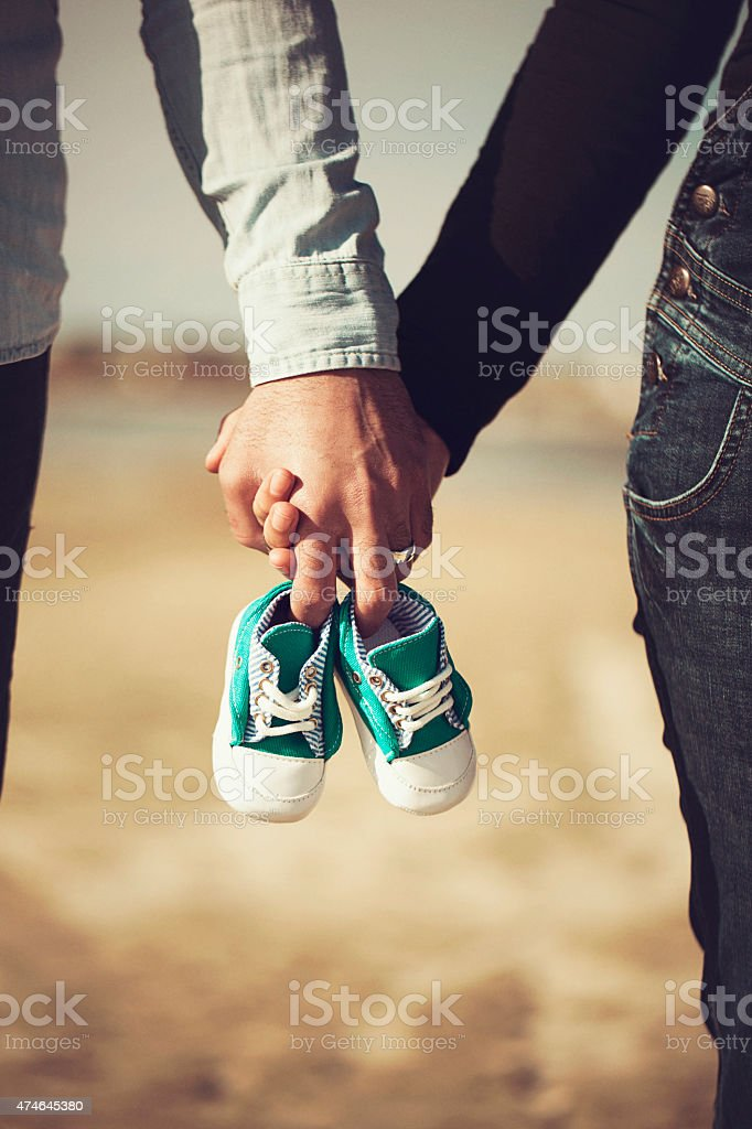Future parents holding hands and a pair of little shoes stock photo