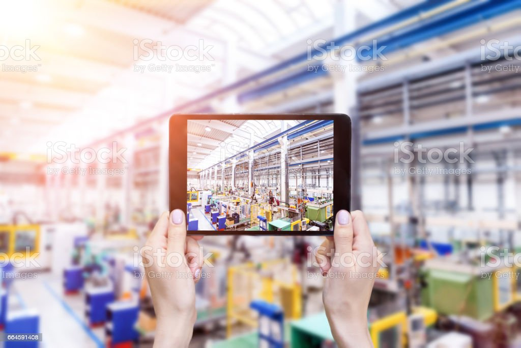 Futuristic factory & hands holding tablet stock photo