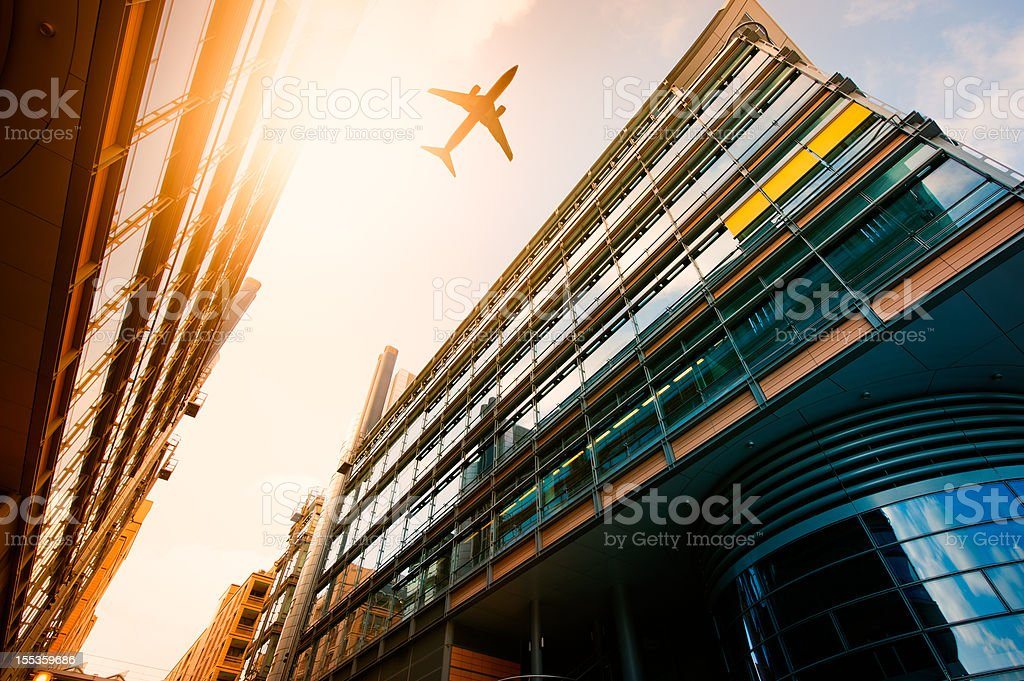 Futuristic office buildings with a airplane silhouette royalty-free stock photo