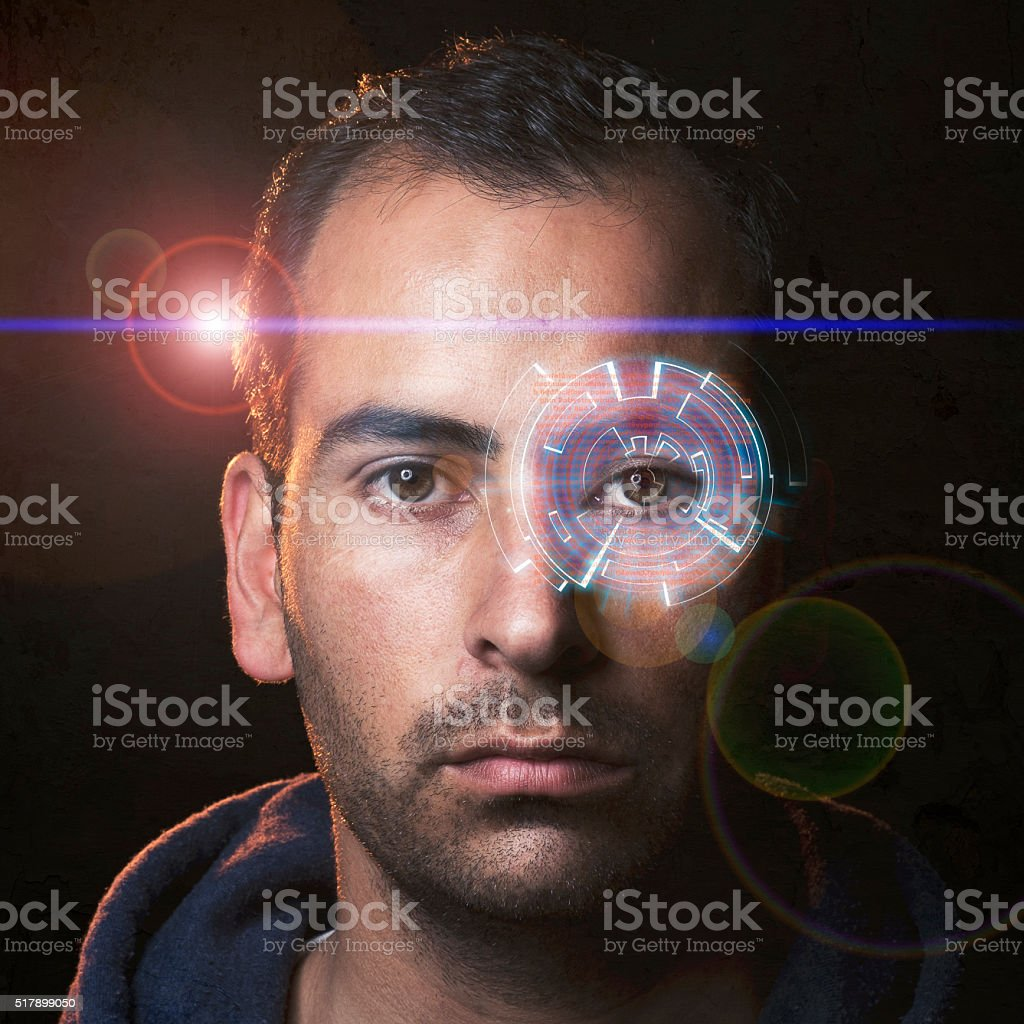 Futuristic young man with a hologram in one eye stock photo