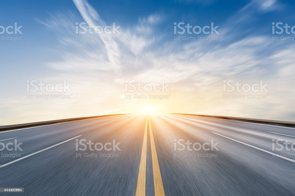 Fuzzy motion asphalt highway scenery at sunset stock photo