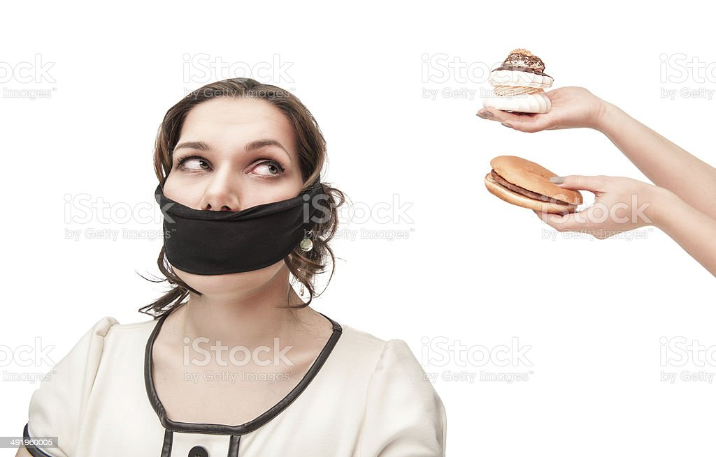 Gagged plus size woman seduced with junk food stock photo