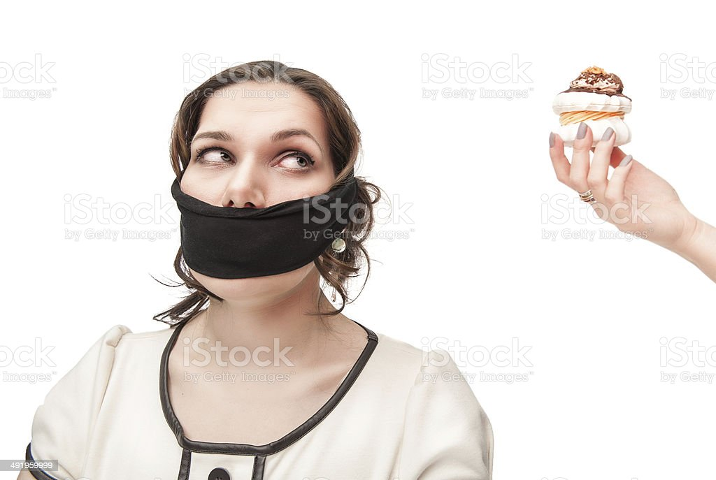 Gagged plus size woman seduced with pastry stock photo