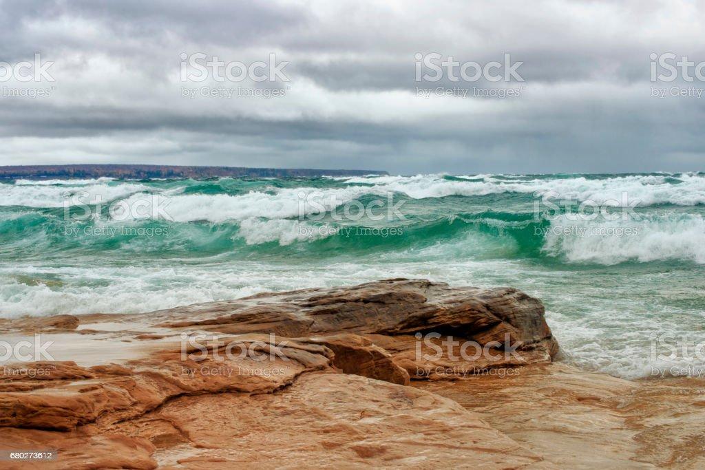 Lake Superior waves crashing upon a rocky shore near Munising,...