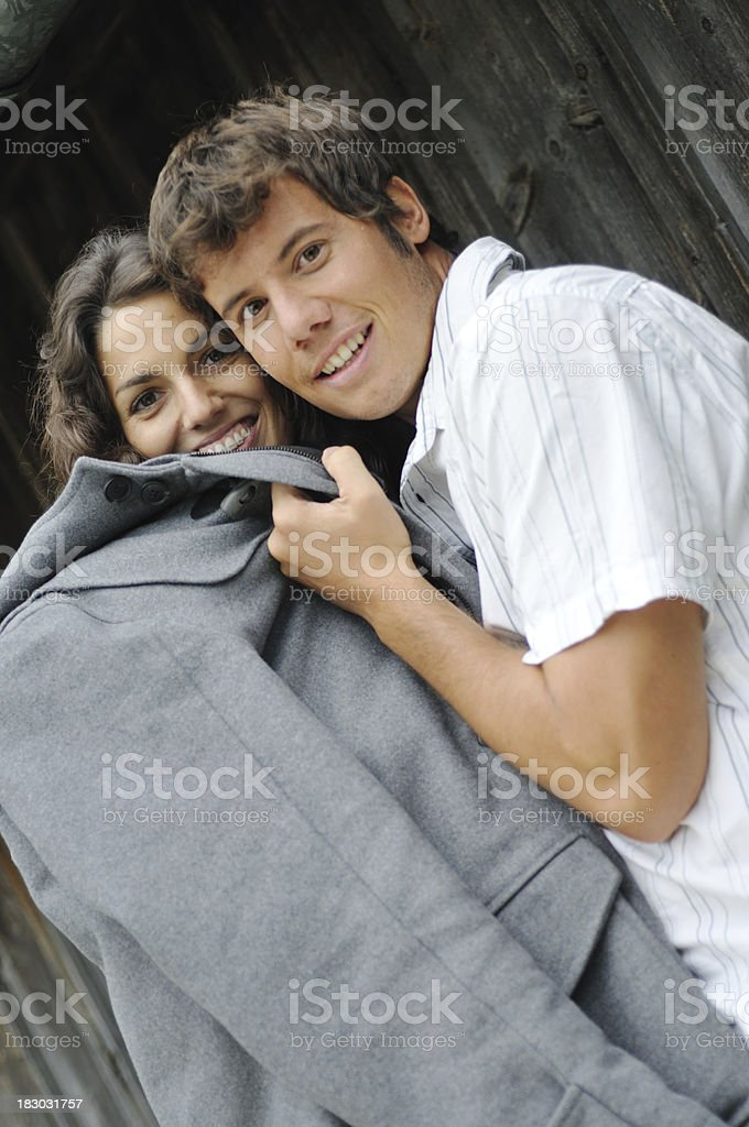 gallant boyfriend gives girl coat stock photo
