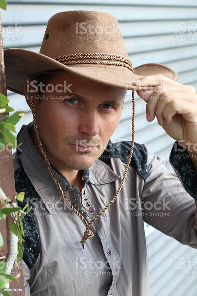 Gallant gentleman in cowboy outfit tipping his hat stock photo