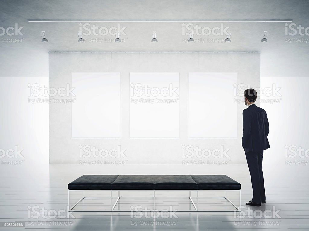 Gallery room and man looking at empty frames stock photo