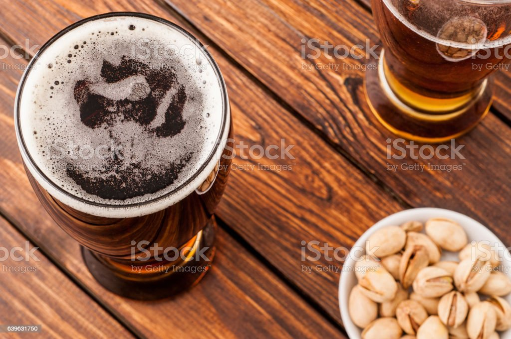 galss of dark cold frothy beer, nuts old wooden table stock photo