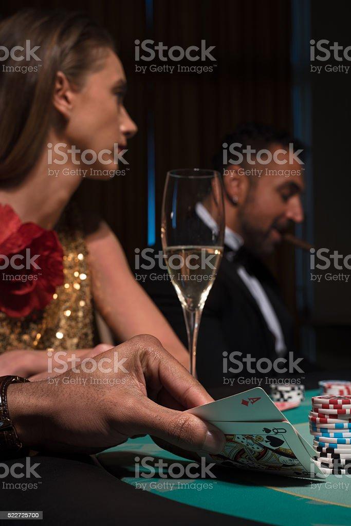 Gambler carefully looking at his winning poker cards stock photo