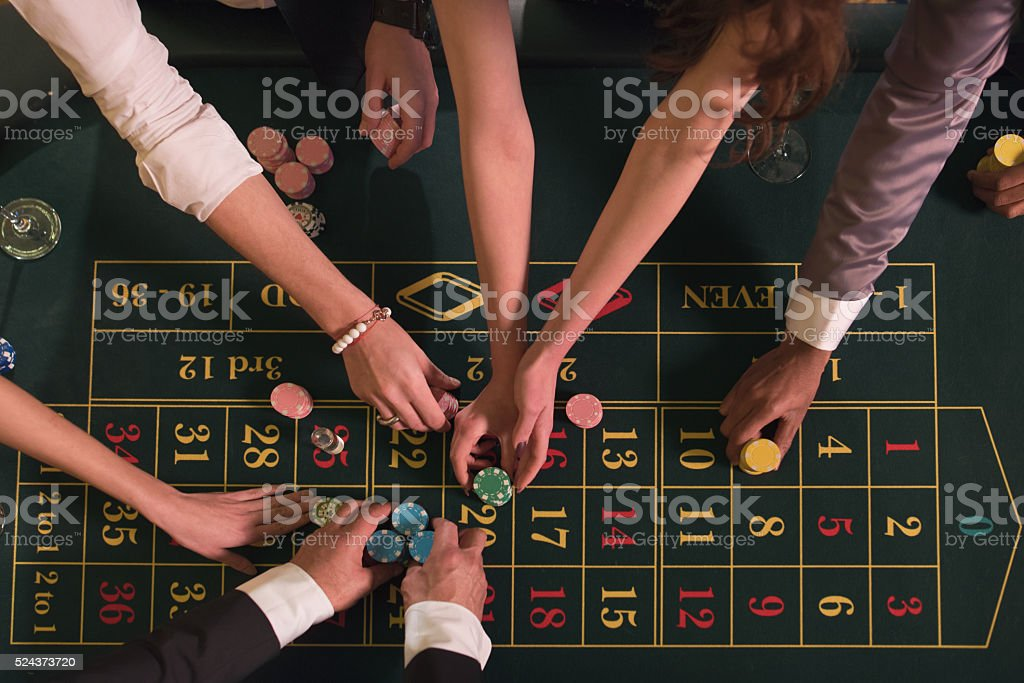 Gamblers placing bets at the casino table stock photo