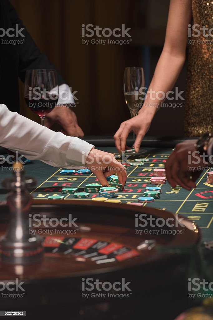 Gamblers placing bets on the roulette table stock photo