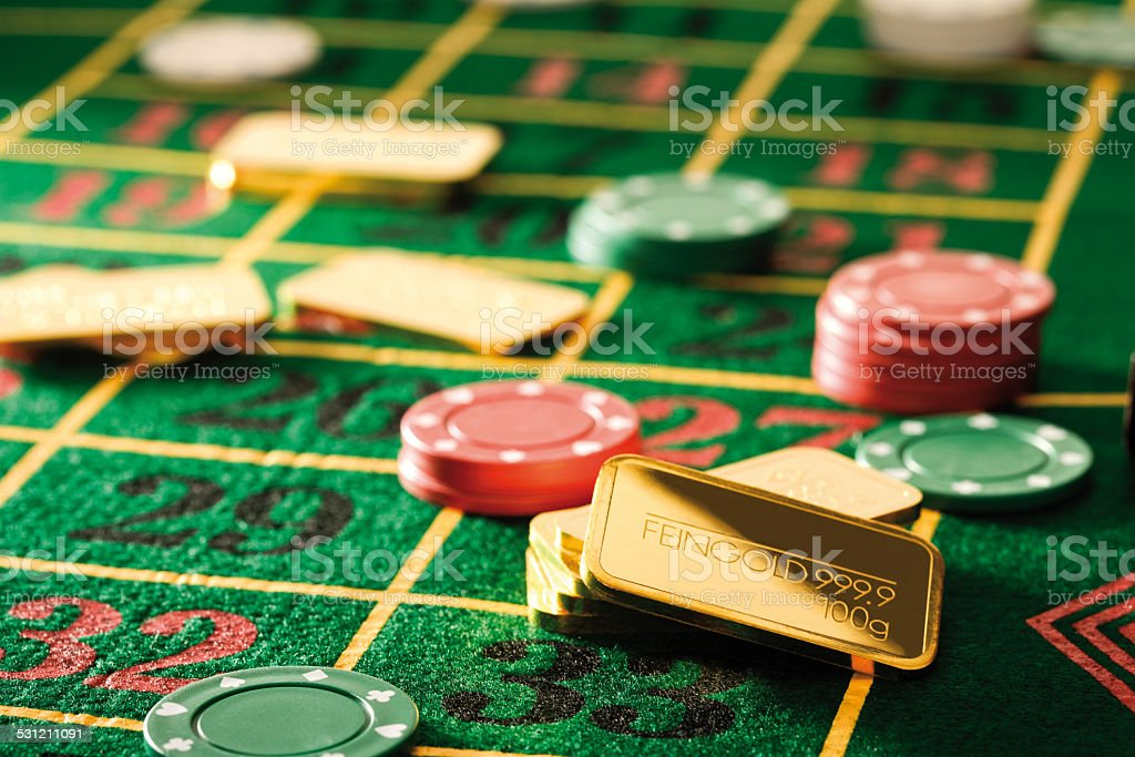 Gambling chips and gold bars on roulette table stock photo
