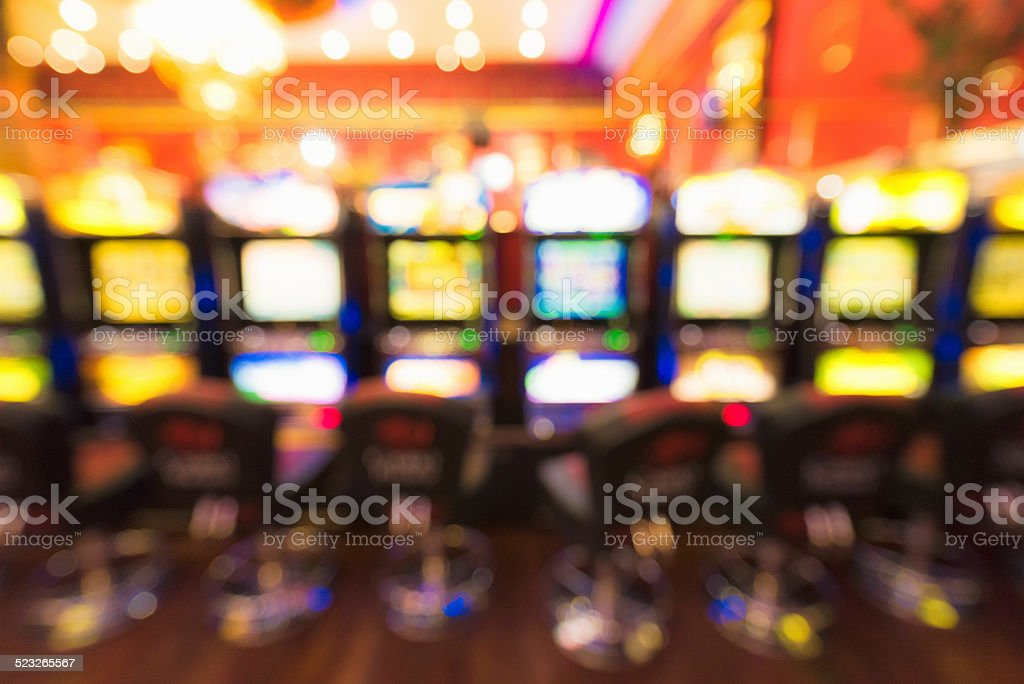 Gambling - defocussed row of casino slot machines stock photo