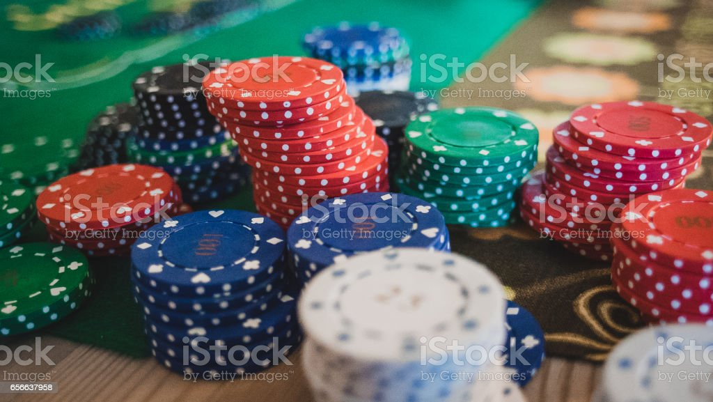 gambling, fortune, game and entertainment concept - close up of casino chips on green table surface stock photo