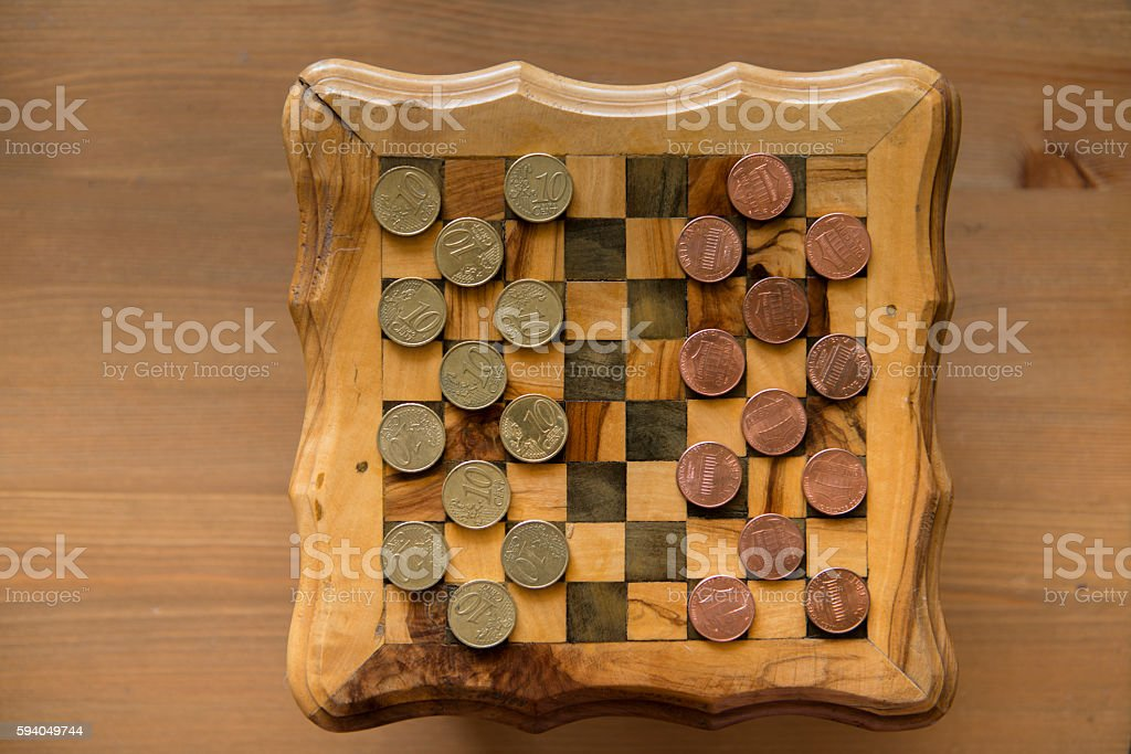 game of checkers - US cents VS eurocents stock photo
