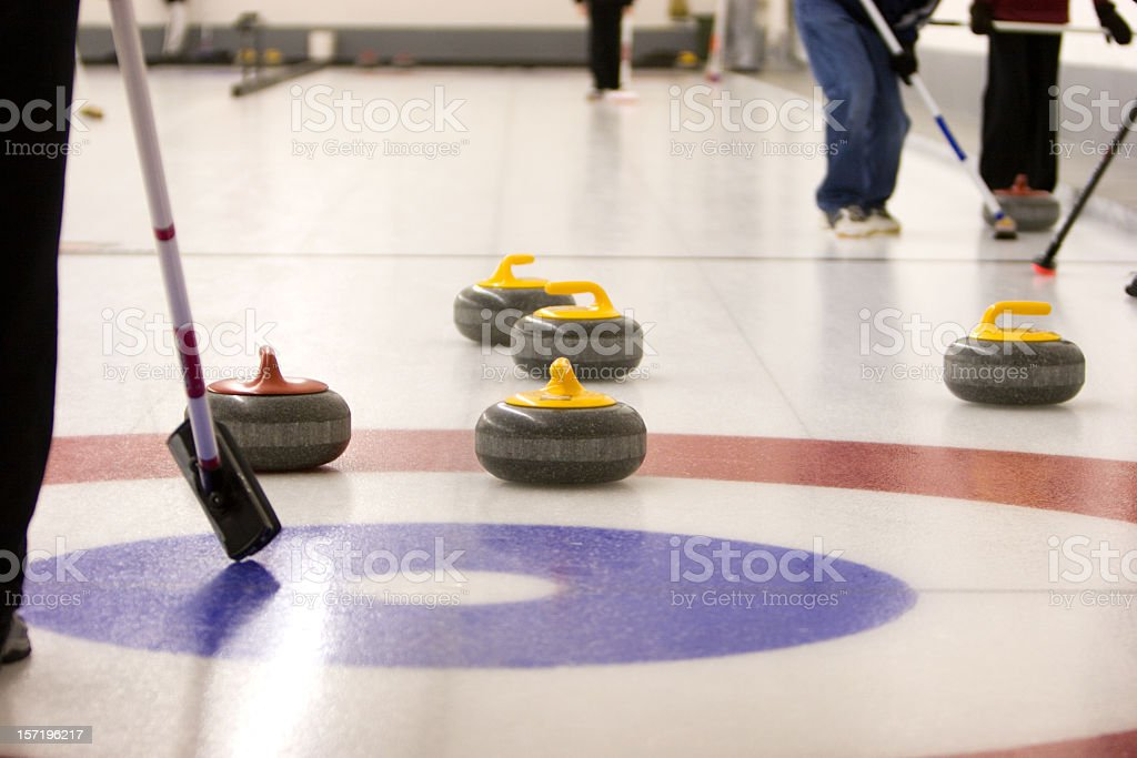 A game of curling on an ice rink with people holding brooms stock photo