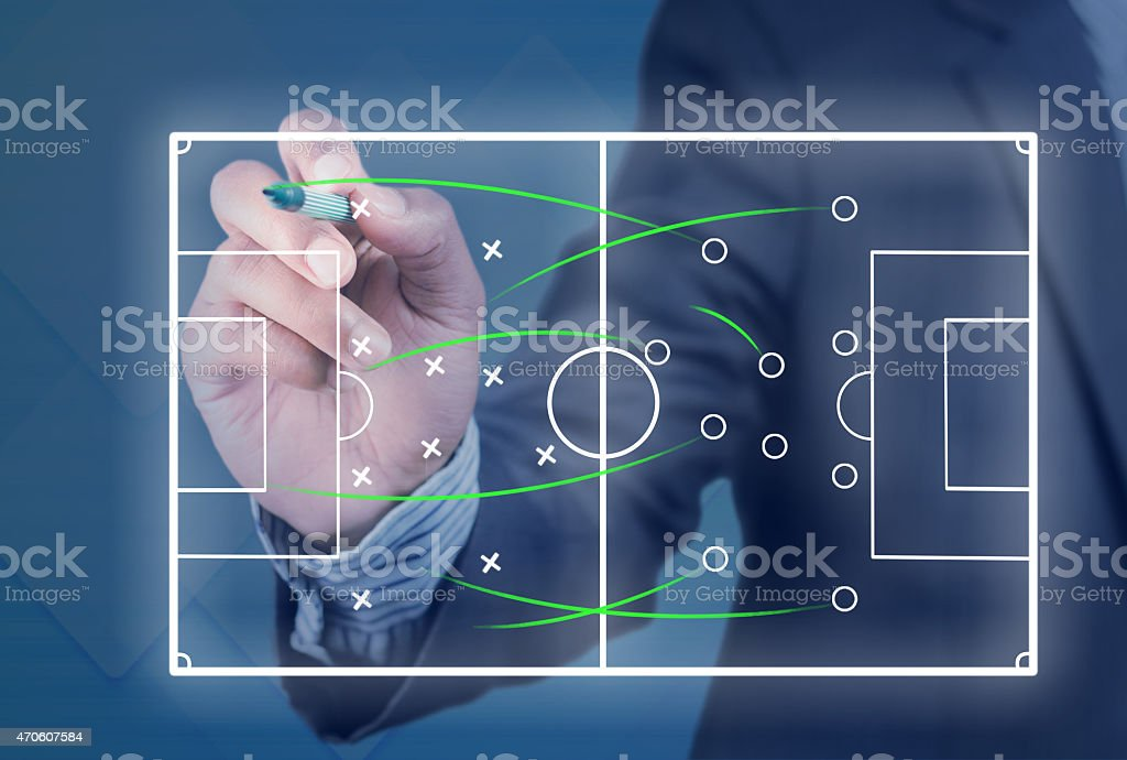 Game plan for a soccer game being edited by a man in a suit stock photo