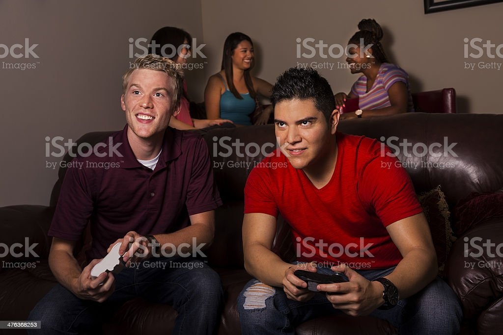 Game:  Two men playing video games. Young women in background. royalty-free stock photo