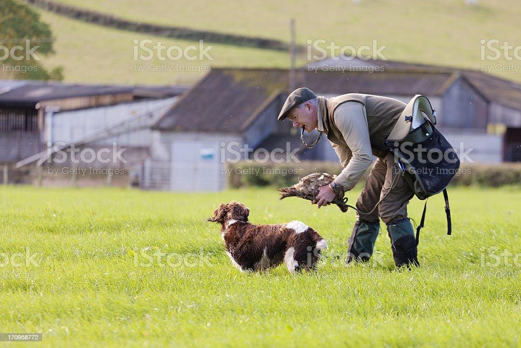Gamekeeper praising his dog stock photo