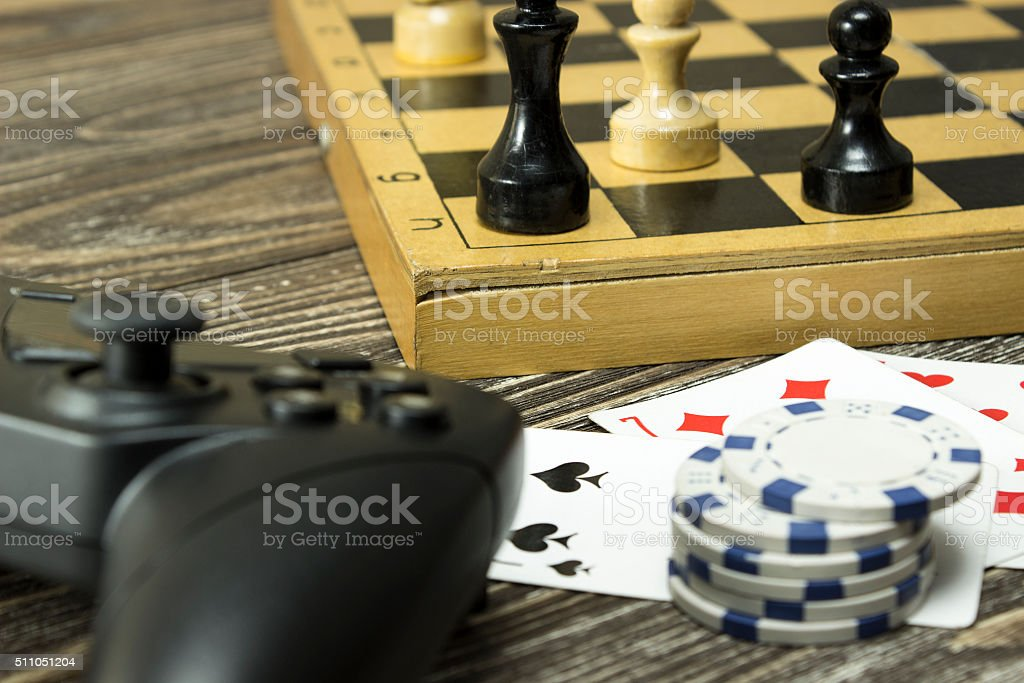 Gamepad, a chess board with figures and playing cards stock photo