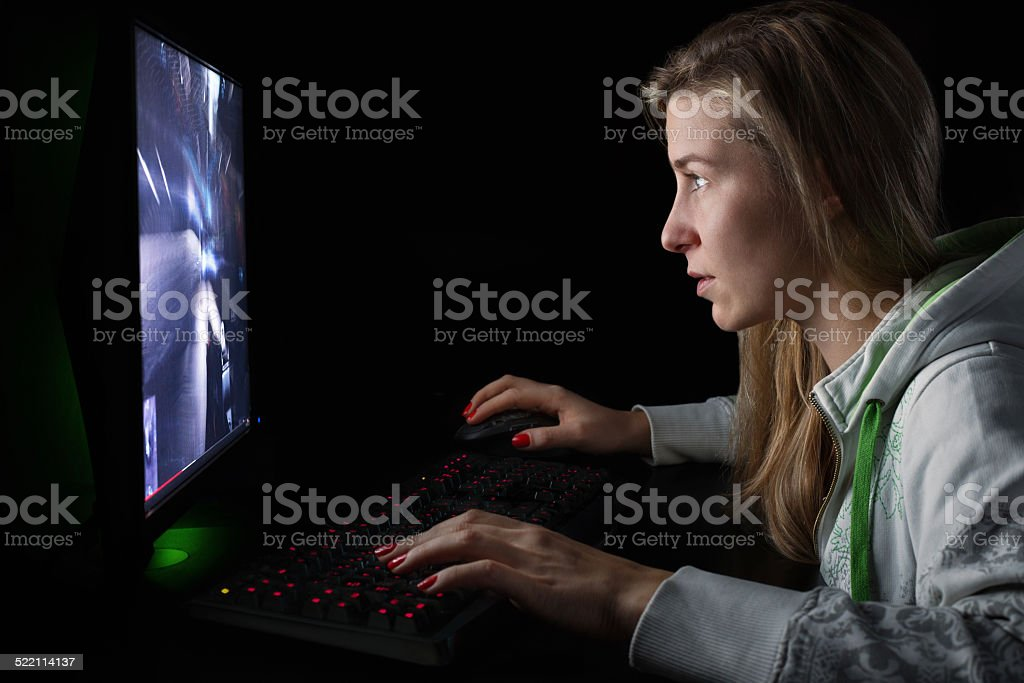 Gamer girl playing first person shooter game stock photo