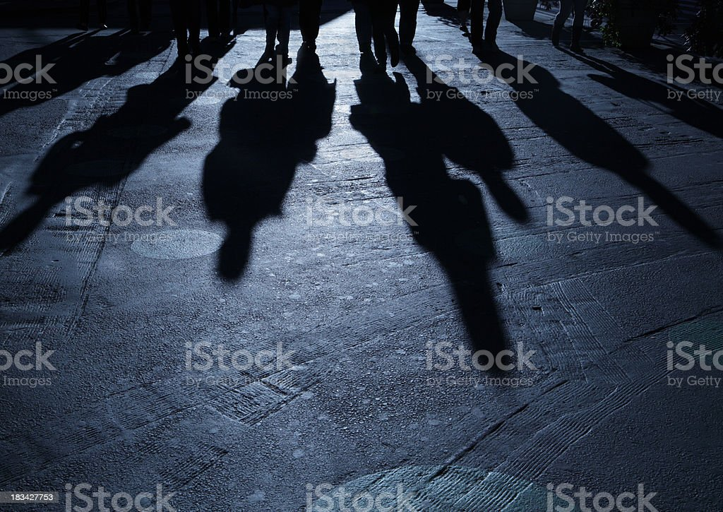 Gang of people advancing on viewer night shadows stock photo