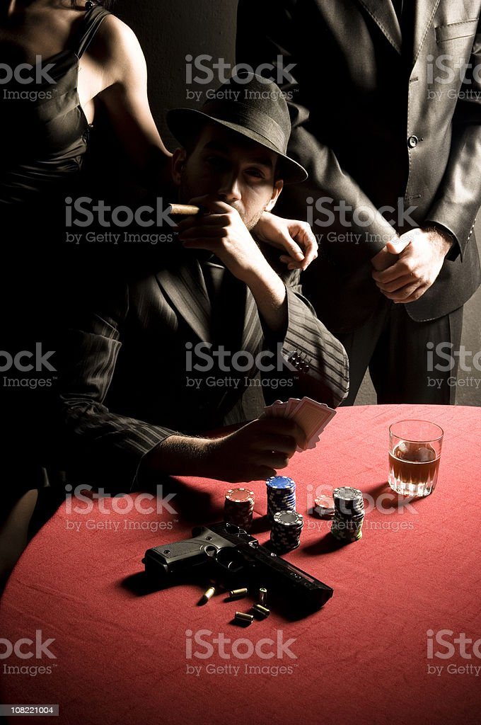 Gangster Man Smoking Cigar and with Gun on Poker Table stock photo