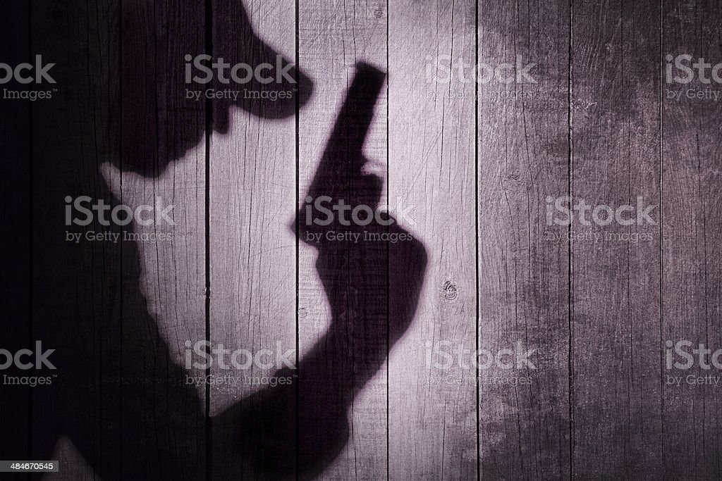 Gangster or investigator or spy silhouette on natural wooden wal stock photo