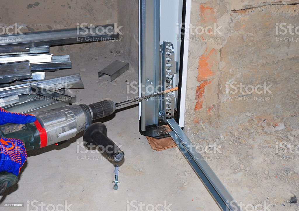 Garage Door Installation. Worker Using Drill stock photo