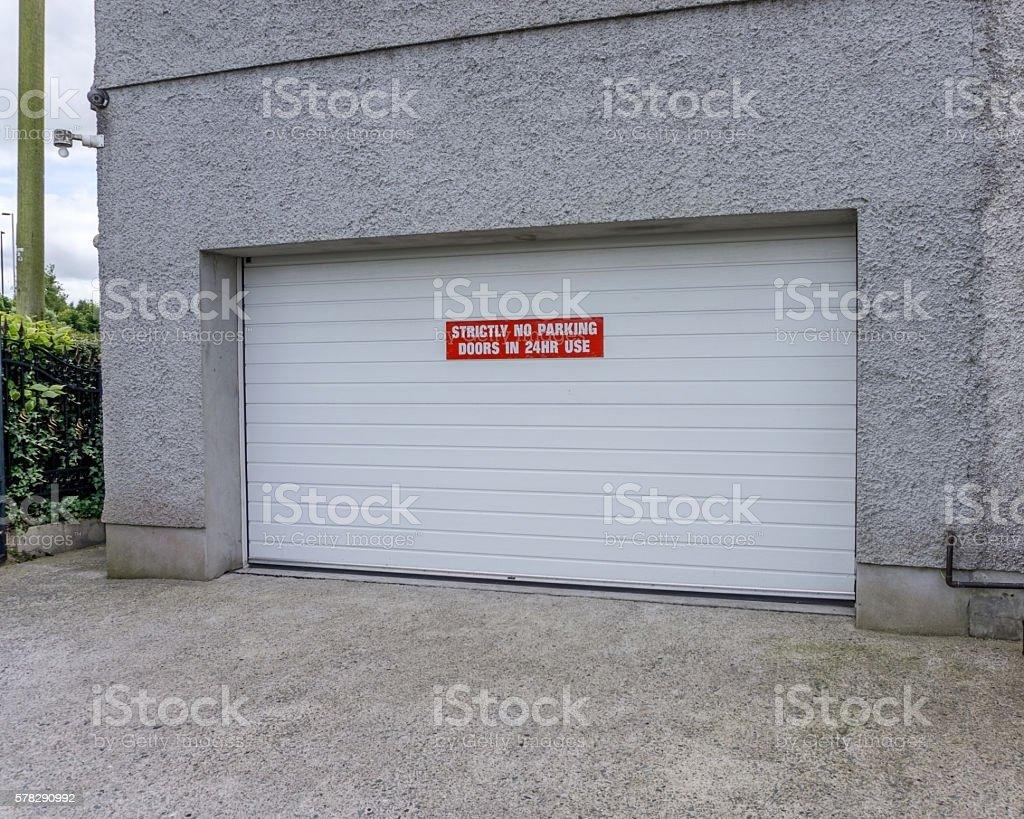 Garage door with red no parking sign stock photo