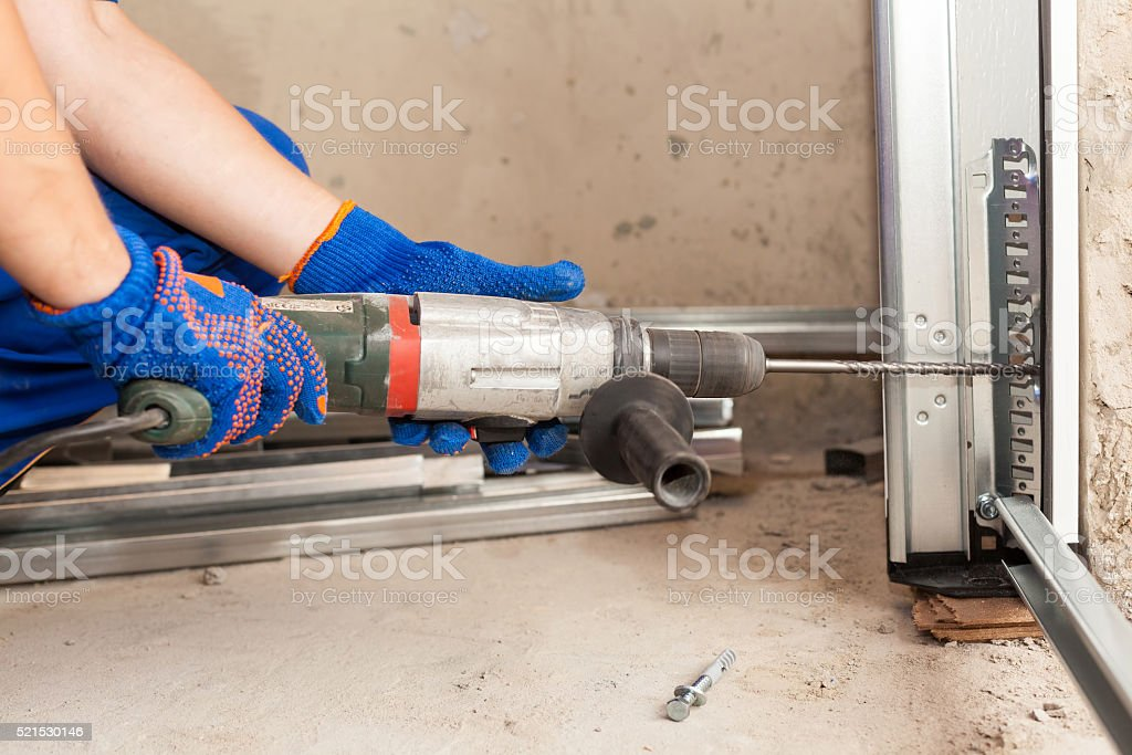 Garage doors installation. Worker drills a hole for the bolt stock photo