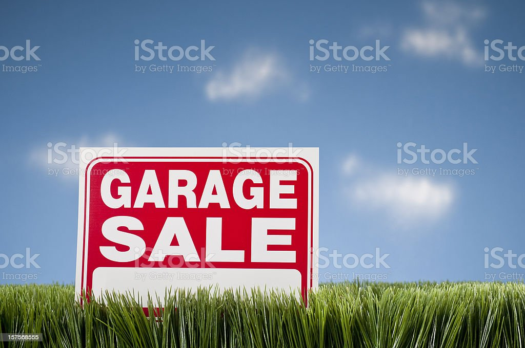 Garage Sale Sign In Grass Against Blue Sky royalty-free stock photo