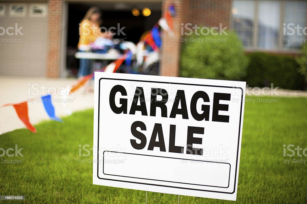 Garage sale sign on the front yard of a suburban house with a woman...