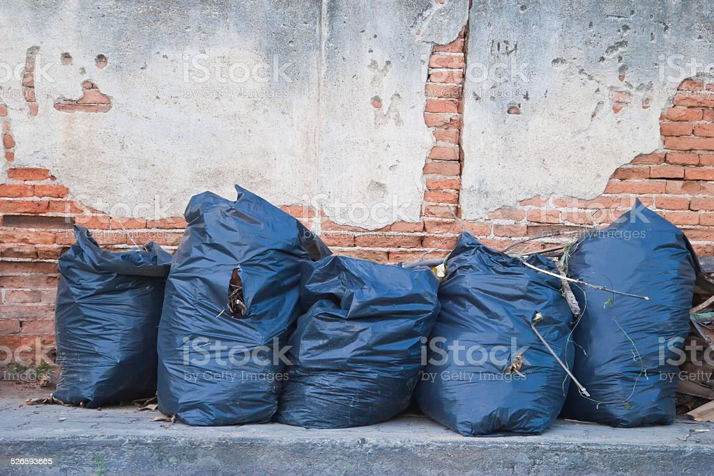 Garbage bags on the old walls. stock photo
