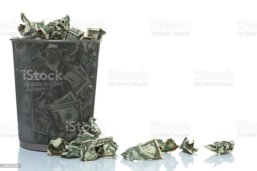 Garbage can full of money spilling over stock photo