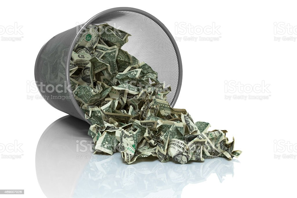 Garbage can full of money tipped on its side stock photo