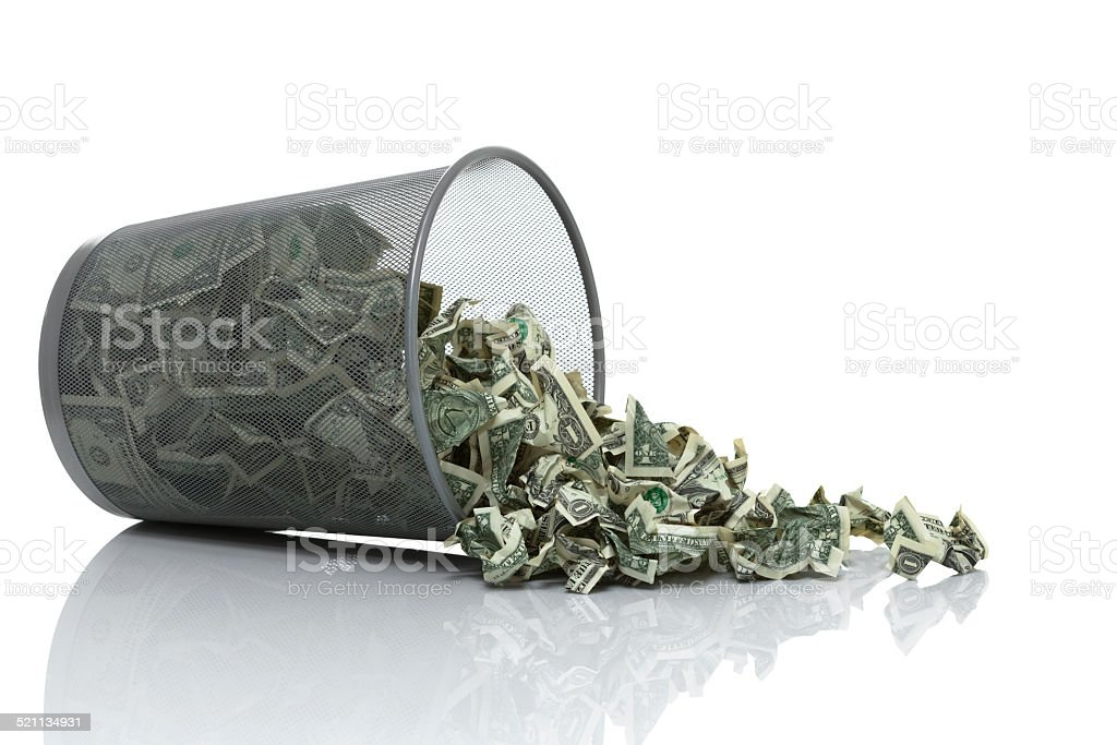 Garbage can full of money tipped on side spilling money stock photo