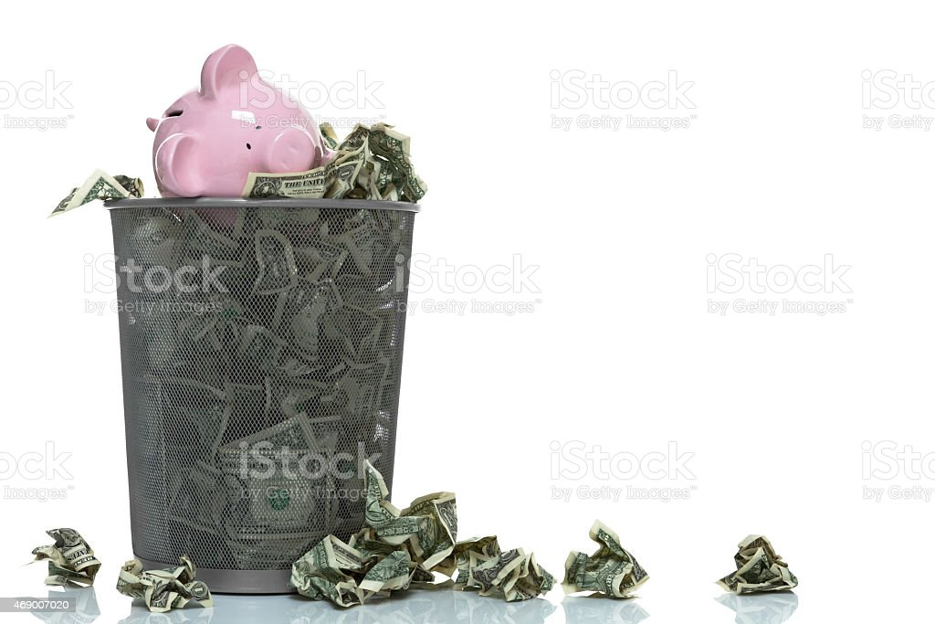 Garbage can full of piggy bank and money spilling over stock photo
