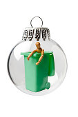 Garbage Can with a Wooden Figure in a Christmas Ornament