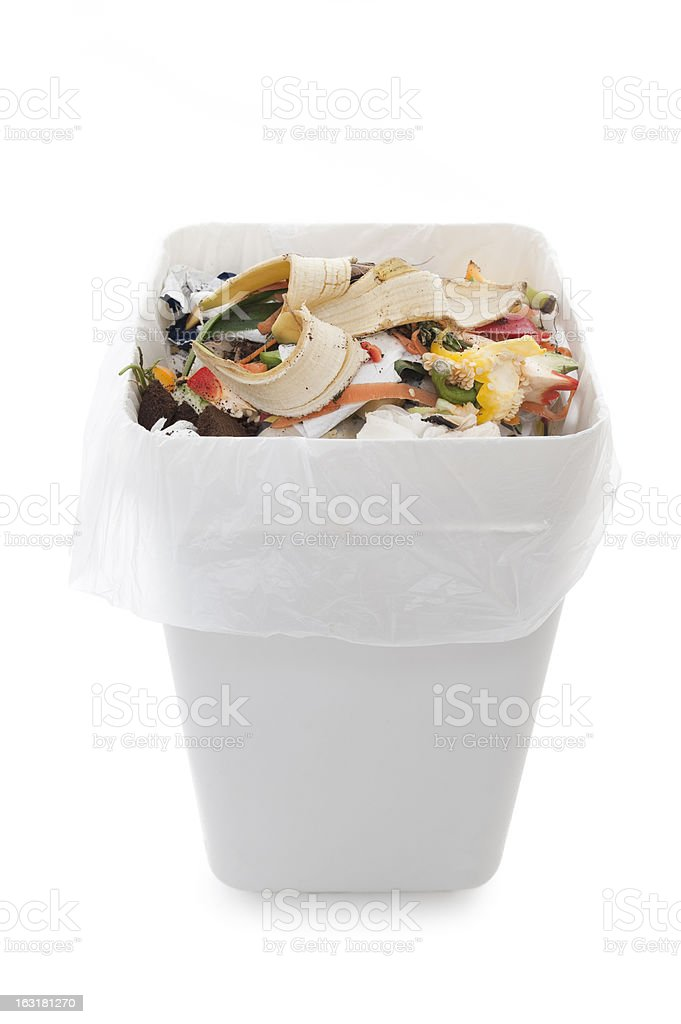 Garbage can with banana peel and food on white background stock photo