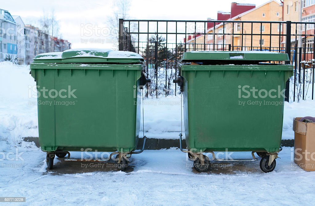 Garbage cans with trash on street winter stock photo