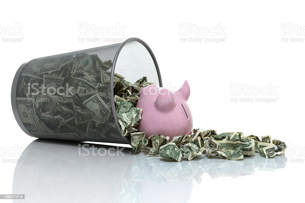 Garbage full of money tipped on side with piggy bank stock photo
