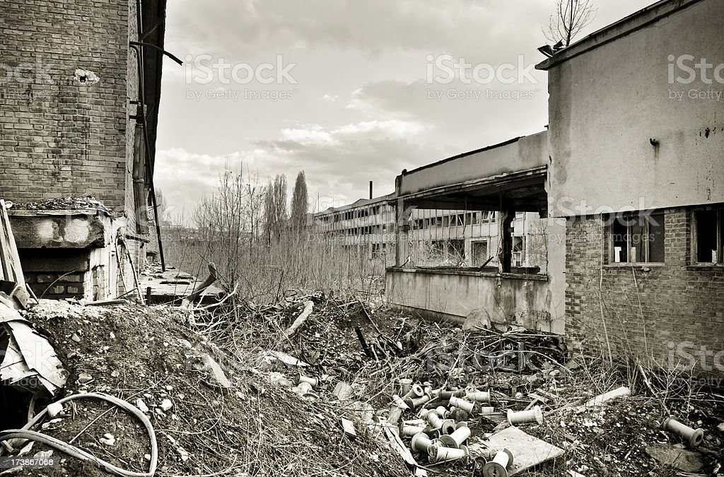 Garbage inside a destroyed factory courtyard on crisis time royalty-free stock photo