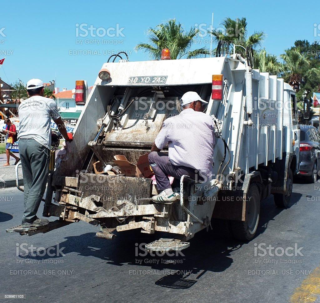 Garbage men behind the garbage truck stock photo