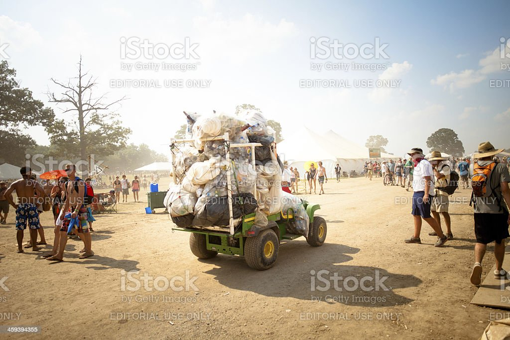 Garbage truck carting off huge pile of waste at festival stock photo